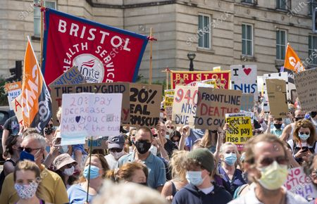 """; Bristol, UK. NHS Workers say NO! at a 'Bristol for Pay Justice' rally and march held in solidarity with health and social care workers across the UK demanding fair recognition of everyone in the NHS family and their tireless work throughout the pandemic. The campaign says """"If you clapped for us, please come and stand with us."""" The campaign says it is a disgrace that so many health and social care staff who worked so hard and risked their lives have been overlooked in the public sector pay rise, and that without nurses, health care assistants, porters, cleaners and the whole NHS family the UK could not have made it through. The campaign says that for too long this work has been underpaid and undervalued and now the UK government is squeezing the NHS from all sides; they say NO to privatisation, deliberate underfunding, low wages and poor conditions. Organisers asked that all attendees respect social distancing as much as possible and with a planned route that gives as much space as possible and that mask wearing will be mandatory with masks available on the day for those that don't have them. Attendees are asked to wear blue, or a blue ribbon in solidarity."""
