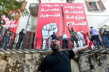 Protesters shout slogans next to banners reading in Arabic (L) 'Beirut capital of revolution' and (R) 'Beirut capital without weapons' as they enter the foreign ministry headquarters during a protest in Beirut, Lebanon, 08 August 2020. People gathered for the so-called 'the Saturday of the hanging ropes' to protest against the political leaders and calling on those responsible over the explosion to be held accountable. Lebanese Health Ministry on 07 August said at least 154 people were killed, and more than 5,000 injured in the Beirut blast that devastated the port area on 04 August and believed to have been caused by an estimated 2,750 tons of ammonium nitrate stored in a warehouse.