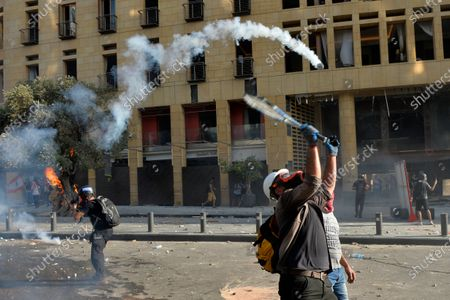 An anti-government protester uses a tennis racket to return a tear gas canister at riot police during a protest outside of the Lebanese Parliament in downtown Beirut, Lebanon, 08 August 2020. People gathered for the so-called 'the Saturday of the hanging ropes' to protest against the political leaders and calling on those responsible over the explosion to be held accountable. Lebanese Health Ministry on 07 August said at least 154 people were killed, and more than 5,000 injured in the Beirut blast that devastated the port area on 04 August and believed to have been caused by an estimated 2,750 tons of ammonium nitrate stored in a warehouse.