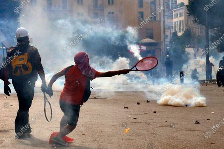 An anti-government protester uses a tennis racket to return a tear gas canister at riot police during a protest outside of the Lebanese Parliament in Beirut, Lebanon, 08 August 2020. People gathered for the so-called 'the Saturday of the hanging ropes' to protest against the political leaders and calling on those responsible over the explosion to be held accountable. Lebanese Health Ministry on 07 August said at least 154 people were killed, and more than 5,000 injured in the Beirut blast that devastated the port area on 04 August and believed to have been caused by an estimated 2,750 tons of ammonium nitrate stored in a warehouse.