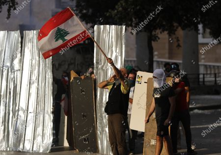 Anti-government protesters wave the Lebanese flag and some hide behind metal panels, as they clash with riot police during a protest against the political elites and the government, in Beirut, Lebanon, . A group of Lebanese protesters including retired army officers have stormed the Foreign Ministry building in the capital Beirut as part of protests following the massive explosion this week