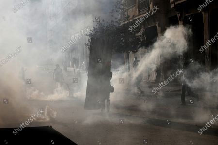Anti-government protesters covered by the smoke of tear gas, as they clash with riot police, during a protest against the political elites and the government, in Beirut, Lebanon