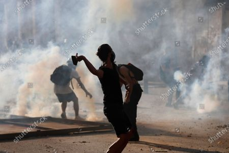 Anti-government protesters are covered by the smoke of tear gas, as they clash with riot police, during a protest against the political elites and the government, in Beirut, Lebanon
