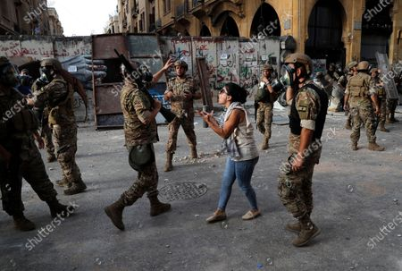 An anti-government protester, reacts in front of Lebanese soldiers during a protest against the political elites and the government, in Beirut, Lebanon