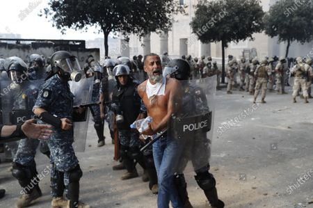 Lebanese riot police arrest an anti-government protester, who was trying to reach the Parliament building, during a protest against the political elites and the government, in Beirut, Lebanon, . A group of Lebanese protesters including retired army officers have stormed the Foreign Ministry building in the capital Beirut as part of protests following the massive explosion this week