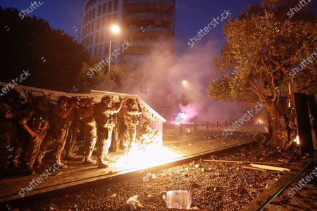 Lebanese security forces take cover during a protest against the political elites and the government after this week's deadly explosion at Beirut port which devastated large parts of the capital and killed more than 150 people, in Beirut, Lebanon