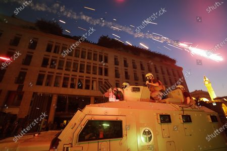 Fireworks go off in front of Lebanese security forces during a protest against the political elites and the government after this week's deadly explosion at Beirut port which devastated large parts of the capital and killed more than 150 people, in Beirut, Lebanon