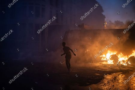 Demonstrator runs from tear gas during a protest against the political elites and the government after this week's deadly explosion at Beirut port which devastated large parts of the capital in Beirut, Lebanon