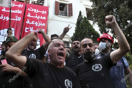 """Retired army officers chant slogans inside the Lebanese foreign ministry in Beirut, Lebanon, . A group of protesters, including retired army officers, in Lebanon stormed the building of the foreign ministry during angry rallies in the capital following the destructive Beirut blast earlier this week. The Arabic posters read, """"Beirut a city free of weapons,"""" right and """"Beirut is the capital of the revolution,"""" left"""