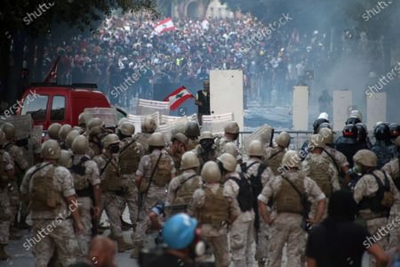 An injured Lebanese anti-government protesters face off with riot police at a protest in Beirut, Lebanon, 08 August 2020. People gathered for the so-called 'the Saturday of the hanging ropes' to protest against the political leaders and calling on those responsible over the explosion to be held accountable. Lebanese Health Ministry on 07 August said at least 154 people were killed, and more than 5,000 injured in the Beirut blast that devastated the port area on 04 August and believed to have been caused by an estimated 2,750 tons of ammonium nitrate stored in a warehouse.