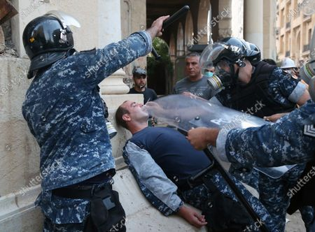 A Lebanese riot policeman is helped during clashes with anti-government protester at a protest in Beirut, Lebanon, 08 August 2020. People gathered for the so-called 'the Saturday of the hanging ropes' to protest against the political leaders and calling on those responsible over the explosion to be held accountable. Lebanese Health Ministry on 07 August said at least 154 people were killed, and more than 5,000 injured in the Beirut blast that devastated the port area on 04 August and believed to have been caused by an estimated 2,750 tons of ammonium nitrate stored in a warehouse.
