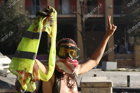 A Lebanese anti-government protester flashes a victory sign and holds a blood-stained yellow jacket of a fellow protester during clashes with riot police at a protest in Beirut, Lebanon, 08 August 2020. People gathered for the so-called 'the Saturday of the hanging ropes' to protest against the political leaders and calling on those responsible over the explosion to be held accountable. Lebanese Health Ministry on 07 August said at least 154 people were killed, and more than 5,000 injured in the Beirut blast that devastated the port area on 04 August and believed to have been caused by an estimated 2,750 tons of ammonium nitrate stored in a warehouse.