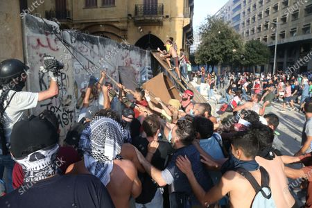 Lebanese anti-government protesters pull a protection wall leading to the Parliament square during a protest in Beirut, Lebanon, 08 August 2020. People gathered for the so-called 'the Saturday of the hanging ropes' to protest against the political leaders and calling on those responsible over the explosion to be held accountable. Lebanese Health Ministry on 07 August said at least 154 people were killed, and more than 5,000 injured in the Beirut blast that devastated the port area on 04 August and believed to have been caused by an estimated 2,750 tons of ammonium nitrate stored in a warehouse.