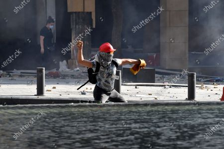 Aa anti-government protesters throws stones at riot police during a protest outside of the Lebanese Parliament in Beirut, Lebanon, 08 August 2020. People gathered for the so-called 'the Saturday of the hanging ropes' to protest against the political leaders and calling on those responsible over the explosion to be held accountable. Lebanese Health Ministry on 07 August said at least 154 people were killed, and more than 5,000 injured in the Beirut blast that devastated the port area on 04 August and believed to have been caused by an estimated 2,750 tons of ammonium nitrate stored in a warehouse.