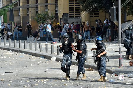 Anti-government protesters throw stones at riot police during a protest outside of the Lebanese Parliament in Beirut, Lebanon, 08 August 2020. People gathered for the so-called 'the Saturday of the hanging ropes' to protest against the political leaders and calling on those responsible over the explosion to be held accountable. Lebanese Health Ministry on 07 August said at least 154 people were killed, and more than 5,000 injured in the Beirut blast that devastated the port area on 04 August and believed to have been caused by an estimated 2,750 tons of ammonium nitrate stored in a warehouse.