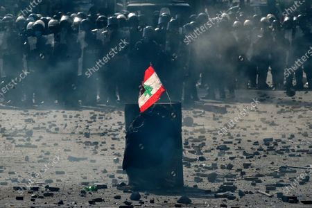 An anti-government protester carries a Lebanese flag as he protects himself behind an iron barrel during a protest outside of the Lebanese Parliament in Beirut, Lebanon, 08 August 2020. People gathered for the so-called 'the Saturday of the hanging ropes' to protest against the political leaders and calling on those responsible over the explosion to be held accountable. Lebanese Health Ministry on 07 August said at least 154 people were killed, and more than 5,000 injured in the Beirut blast that devastated the port area on 04 August and believed to have been caused by an estimated 2,750 tons of ammonium nitrate stored in a warehouse.
