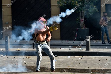 An anti-government protester throws back a tear gas canister against the riot police during during a protest outside of the Lebanese Parliament in Beirut, Lebanon, 08 August 2020. People gathered for the so-called 'the Saturday of the hanging ropes' to protest against the political leaders and calling on those responsible over the explosion to be held accountable. Lebanese Health Ministry on 07 August said at least 154 people were killed, and more than 5,000 injured in the Beirut blast that devastated the port area on 04 August and believed to have been caused by an estimated 2,750 tons of ammonium nitrate stored in a warehouse.