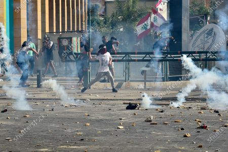 Anti-government protesters throw stones at riot police during a protest outside of the outside of the Lebanese Parliament in Beirut, Lebanon, 08 August 2020. People gathered for the so-called 'the Saturday of the hanging ropes' to protest against the political leaders and calling on those responsible over the explosion to be held accountable. Lebanese Health Ministry on 07 August said at least 154 people were killed, and more than 5,000 injured in the Beirut blast that devastated the port area on 04 August and believed to have been caused by an estimated 2,750 tons of ammonium nitrate stored in a warehouse.