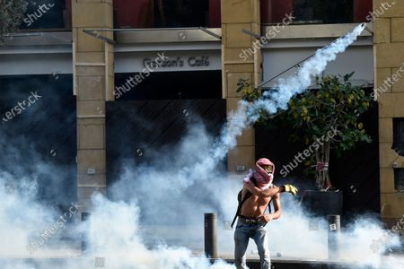An anti-government protester throws back a tear gas canister against the riot police during a protest outside of the Lebanese Parliament in Beirut, Lebanon, 08 August 2020. People gathered for the so-called 'the Saturday of the hanging ropes' to protest against the political leaders and calling on those responsible over the explosion to be held accountable. Lebanese Health Ministry on 07 August said at least 154 people were killed, and more than 5,000 injured in the Beirut blast that devastated the port area on 04 August and believed to have been caused by an estimated 2,750 tons of ammonium nitrate stored in a warehouse.