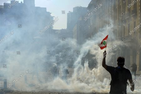 An anti-government protester carries a Lebanese flag during a protest outside of the Lebanese Parliament in Beirut, Lebanon, 08 August 2020. People gathered for the so-called 'the Saturday of the hanging ropes' to protest against the political leaders and calling on those responsible over the explosion to be held accountable. Lebanese Health Ministry on 07 August said at least 154 people were killed, and more than 5,000 injured in the Beirut blast that devastated the port area on 04 August and believed to have been caused by an estimated 2,750 tons of ammonium nitrate stored in a warehouse.