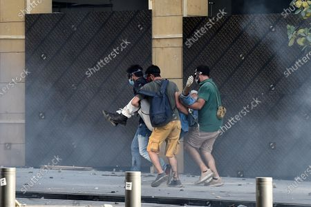 An injured demonstrator is being helped during a protest outside of the Lebanese Parliament in Beirut, Lebanon, 08 August 2020. People gathered for the so-called 'the Saturday of the hanging ropes' to protest against the political leaders and calling on those responsible over the explosion to be held accountable. Lebanese Health Ministry on 07 August said at least 154 people were killed, and more than 5,000 injured in the Beirut blast that devastated the port area on 04 August and believed to have been caused by an estimated 2,750 tons of ammonium nitrate stored in a warehouse.