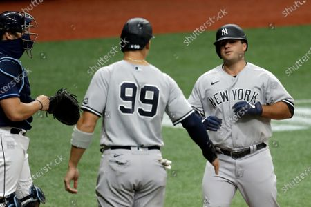 New York Yankees' Mike Ford, right, celebrates with Aaron Judge after Ford hit a two-run home run off Tampa Bay Rays starting pitcher Tyler Glasnow during the third inning of the first game of a baseball doubleheader game, in St. Petersburg, Fla