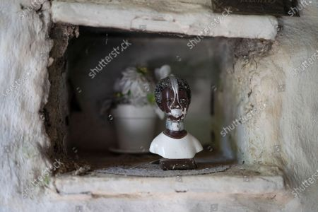 Stock Image of Bust representing Anastacia, an enslaved African woman venerated by devotees of the Umbanda religion, is displayed in a niche in the home of 25-year-old Hugo do Nascimento who died from the new coronavirus, in Rio de Janeiro, Brazil, . Brazil was leaping toward a grim milestone, 100,000 deaths from COVID-19, on Saturday, Aug. 8, and five months after the first reported case, the country had not shown signs of crushing the disease