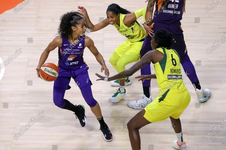 Phoenix Mercury's Skylar Diggins-Smith, left, looks between the defense of Seattle Storm's Jordin Canada, center, and Natasha Howard, right, during the first half of a WNBA basketball game, in Bradenton, Fla
