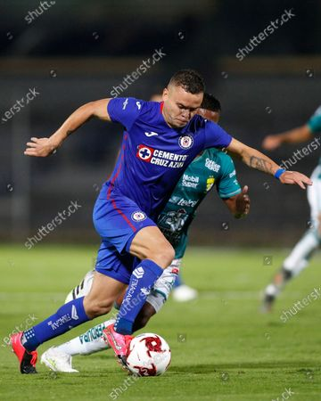Cruz Azul's Jonathan Rodríguez, front, and Leon's Pedro Aquino compete for the ball during a Mexican soccer league match at University Olympic Stadium in Mexico City, . The match was played behind closed doors as a precaution against the new coronavirus