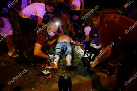 Paramedics treat a wounded person after clashes with police man in Minsk, Belarus, . Police and protesters clashed in Belarus' capital and the major city of Brest on Sunday after the presidential election in which the authoritarian leader who has ruled for a quarter-century sought a sixth term in office