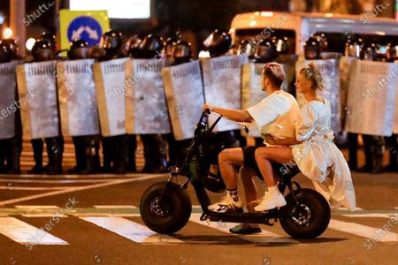 Couple ride a scooter in front of a line of police officers as others gather to protest against a result of the Belarusian presidential election in Minsk, Belarus, . Police and protesters clashed in Belarus' capital and the major city of Brest on Sunday after the presidential election in which the authoritarian leader who has ruled for a quarter-century sought a sixth term in office