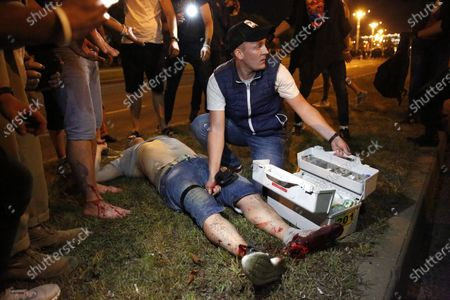 An injured protester gets help during clashes with riot police during a protest after polling stations closed at the presidential elections in Minsk, Belarus, late 09 August 2020. Five candidates are contesting for the presidential seat, including the incumbent president Lukashenko.