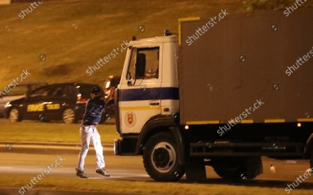 An opposition activist tries to stop a police truck during a protest after polling stations closed at the presidential elections in Minsk, Belarus, 09 August 2020. Five candidates are contesting for the presidential seat, including the incumbent president Lukashenko.