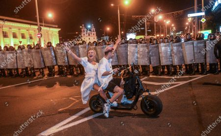 Protesters ride an electric bike in front of police during a protest after polling stations closed at the presidential elections in Minsk, Belarus, 09 August 2020. Five candidates are contesting for the presidential seat, including the incumbent president Lukashenko.