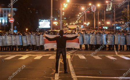 A demonstrator holds a flag in front of police during a protester after polling stations closed at the presidential elections in Minsk, Belarus, 09 August 2020. Five candidates are contesting for the presidential seat, including the incumbent president Lukashenko.