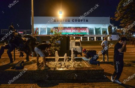 Protesters try to clean thier eyes from tear gas during a protest after polling stations closed at the presidential elections in Minsk, Belarus, 09 August 2020. Five candidates are contesting for the presidential seat, including the incumbent president Lukashenko.
