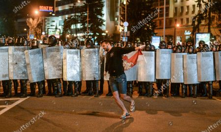 A demonstrator holds a flag in front of riot police during a protest after polling stations closed in the presidential elections, in Minsk, Belarus, 09 August 2020. Five candidates are contesting for the presidential seat, including the incumbent president Lukashenko.