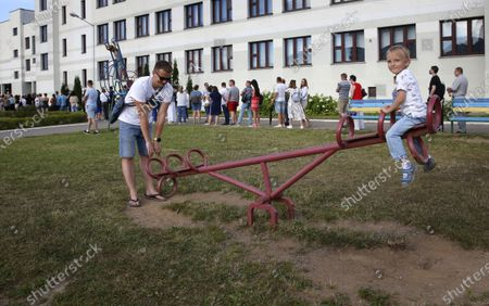 A man plays with a child at playground as he waits in line outside a polling station to cast his vote during the presidential elections in Minsk, Belarus, 09 August 2020. Five candidates are contesting for the presidential seat, including the incumbent president Alexander Lukashenko.
