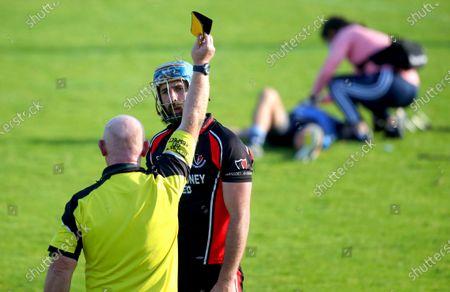 Stock Image of St. Anne's vs Oulart The Ballagh. Referee David Jenkins shows Oulart The Ballagh's Garrett Sinnott a yellow card