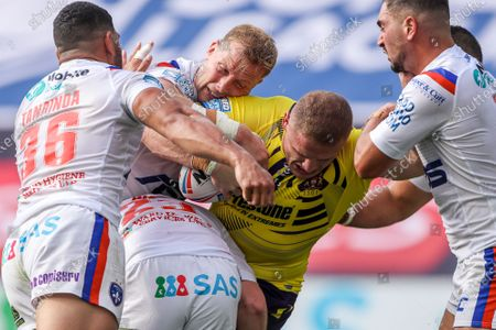 Stock Photo of Wigan's George Burgess is tackled by Wakefield's Josh Wood, Craig Kopczak, Kelepi Tanginoa and Tony Gigot.