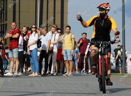 Man rides a bike and takes pictures as people queue to cast their votes in the Belarusian presidential election in Minsk, Belarus, . Belarusians are voting on whether to grant incumbent president Alexander Lukashenko a sixth term in office, extending his 26-years rule, following a campaign marked by unusually strong demonstrations by opposition supporters