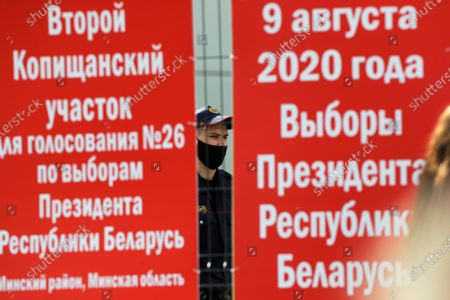 """Police officer stands behind a fence of a polling station during the Belarusian presidential election in Minsk, Belarus, . Banners read at left: """"Second Kopyshansky polling station N26 for the election of President of the Republic of Belarus, Minsk's district of Minsk region"""", and at right, """"9 of August 2020 year. The election of President of the Republic of Belarus"""". Belarusians are voting on whether to grant incumbent president Alexander Lukashenko a sixth term in office, extending his 26-years rule, following a campaign marked by unusually strong demonstrations by opposition supporters"""