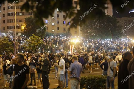 Protesters light up their mobile devices as they gather after the Belarusian presidential election in Minsk, Belarus, . Police and protesters clashed in Belarus' capital and the major city of Brest on Sunday after the presidential election in which the authoritarian leader who has ruled for a quarter-century sought a sixth term in office