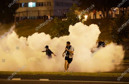 Protesters run through smoke during a protest after the Belarusian presidential election in Minsk, Belarus, . Police and protesters clashed in Belarus' capital and the major city of Brest on Sunday after the presidential election in which the authoritarian leader who has ruled for a quarter-century sought a sixth term in office