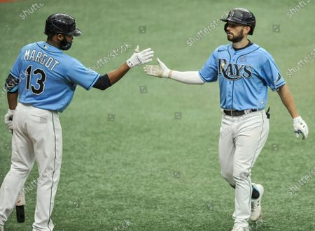Tampa Bay Rays' Manuel Margot, left, congratulates Brandon Lowe, right, after Lowe's solo home run off New York Yankees starter James Paxton during the seventh inning of a baseball game, in St. Petersburg, Fla