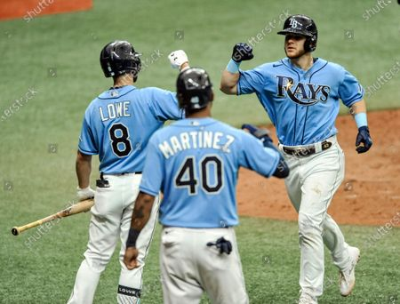 Tampa Bay Rays' Brandon Lowe (8) and Jose Martinez (40) congratulate Michael Brosseau, right, after his two-run home run off New York Yankees starter James Paxton during the seventh inning of a baseball game, in St. Petersburg, Fla