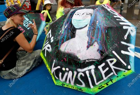 A protestor sits next to an umbrella depicting the Mona Lisa with a face mask during a demonstration of artists calling for more financial support to face the crisis caused by the coronavirus pandemic, in Berlin, Germany, 09 August 2020. Musicians, actors, and performers call for more support from the authorities as many artists struggle to make a living under the effects of the Covid-19 disease pandemic.