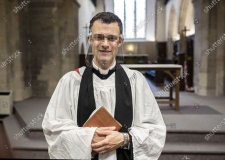 Stock Picture of The Vicar  Ben Read poses wearing his face mask after  morning prayers at St.Mary's Church Kingsclere, Hants.