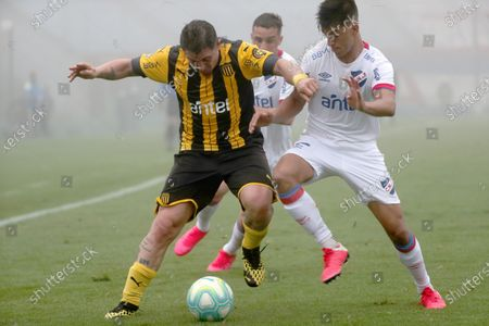Mathias Laborda (R) of Nacional vies for the ball with Cristian Rodriguez of Penarol during the Uruguayan League Apertura tournament soccer match between Club Nacional and Penarol at Centenario stadium in Montevideo, Uruguay, 09 August 2020. The League resumed competition after having been suspended almost five months due to the coronavirus pandemic.