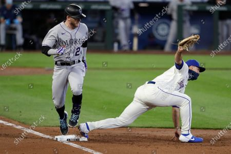 Colorado Rockies' Trevor Story, left, looks at Seattle Mariners first baseman Evan White after grounding out in the third inning of a baseball game, in Seattle